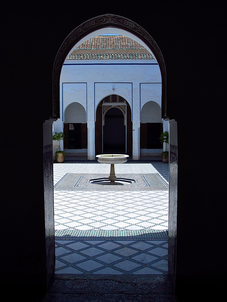 In the middle of the courtyard is a large rectangular fountain with a smaller round basin at its center. The courtyard is surrounded by open-air galleries roofed in green ceramic tile. The arches that support the inner sides of the galleries feature bright yellow and blue ceramic screens inset above their imposts.