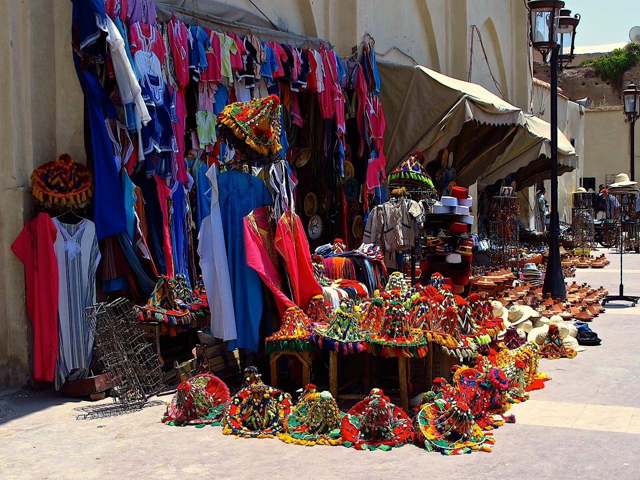 "Hats worn by ""water sellers"" adorn this souvenir stand outside of the mosque."