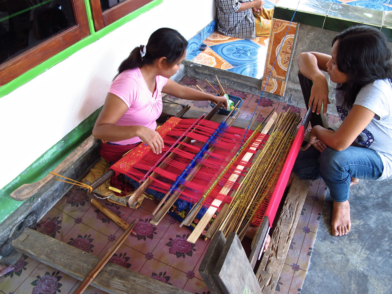 Two main villages on Lombok are known for it's traditional weaving.  One is Sukarara, pictured here in Central Lombok. Typical sarongs and tenun ikat are produced here. The sarong is not only a comfortable article of clothing but can serve as a sheet, towel and multitude of other uses. <br /> <br /> Songket is a fabric that is hand-woven in silk or cotton, and intricately patterned with gold or silver threads. The metallic threads stand out against the background cloth to create a shimmering effect. In the weaving process the metallic threads are inserted in between the silk or cotton weft (latitudinal) threads. It is one of the most complicated hand weaving that usually done by women from generation to generation. The process can take over a month to create one piece of songket.
